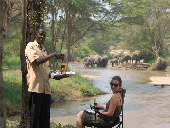 Ishasha Wilderness Camp - guest + elephant crossing river