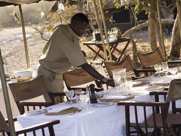 Chobe Under Canvas - staff laying table