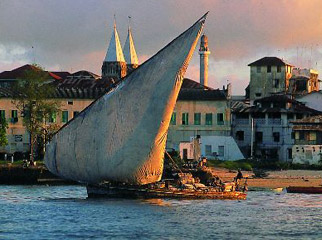 Tanzania in One Country - a dhow sails through the bay of Stone Town, Zanzibar