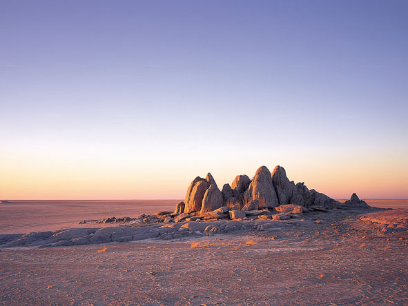 Enigmatic rock islands rise out of pancake-flat salt pans - the Kalahari is a place of surprises.