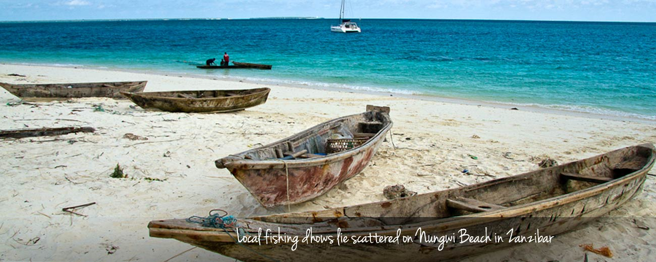 Local fishing dhows lie scattered on Nungwi Beach in Zanzibar.