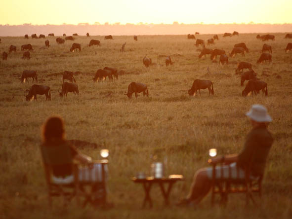 Enjoy a sundowner drink with an unbeatable backdrop: the wildebeest migration.