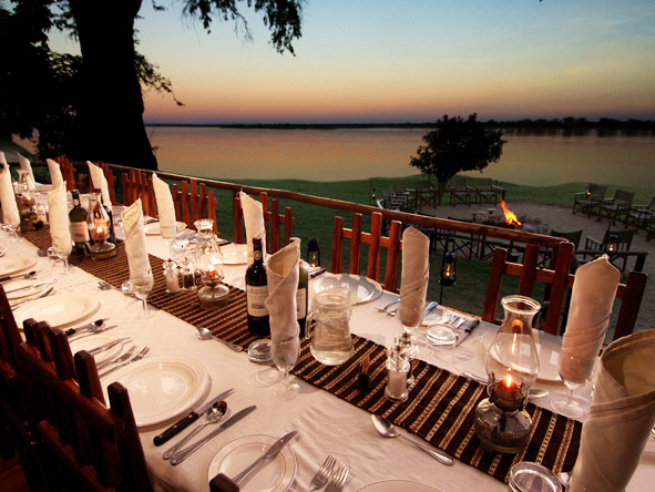 Firelight & tall drinks start the evening in the Lower Zambezi; white linen & candlelight await.