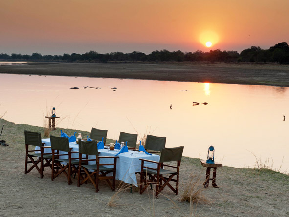 Sunset next to the Luangwa River & a table laid for a starlit dinner - safaris don't get better than this.