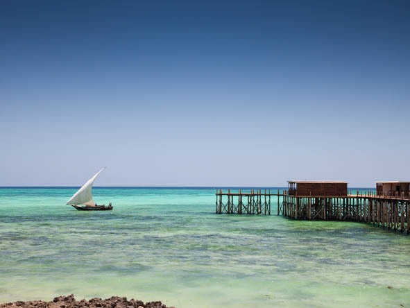 Azure ocean views & the white, fin-shaped sail of a dhow: the soothing colours of a Zanzibar holiday.