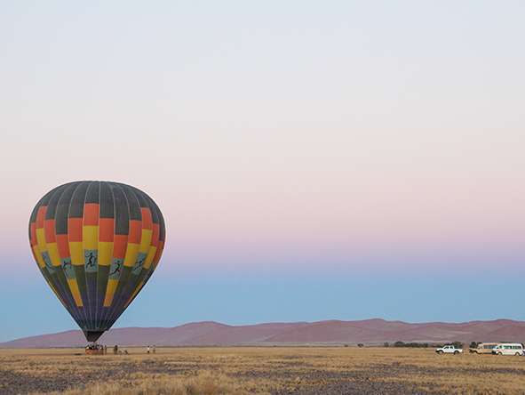Distant mountains glow pink during a dawn balloon flight in Namibia.
