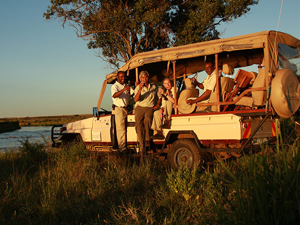 An afternoon Lemala game drive ends with traditional 'sundowners' - served with a smile.