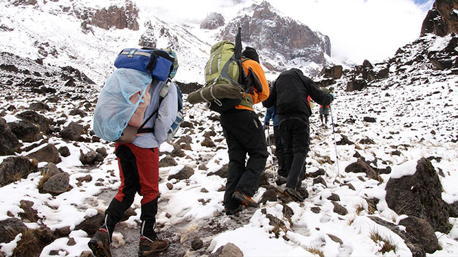 Make it Up Kilimanjaro - porters in the snow