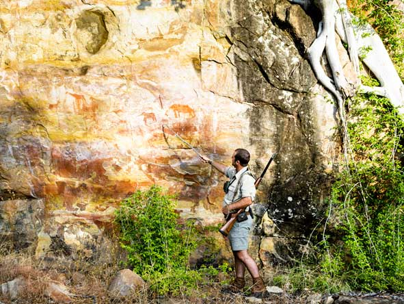 safari ranger looking at bushman rock art